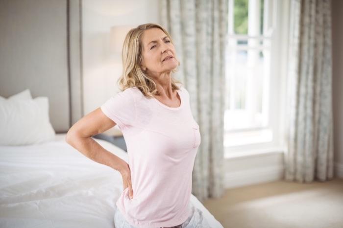 Femme qui a un mal de dos au réveil